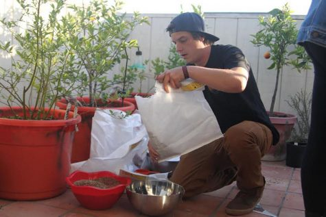Botany Club president Tim Sisneros pours and mixes wildflower seeds into bowls on Wednesday, April 12, on Chapala street in Santa Barbara. Club members used the seeds to make seed bombs, small absorbent balls made of paper, clay or compost that contain seeds.