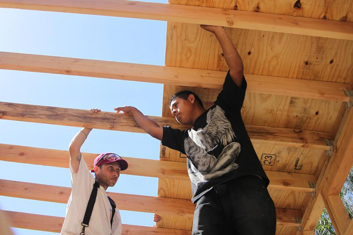 First-year construction students Nathan McBrayer and Jonathan Pena hold onto the wood panels inside the tiny house on Saturday, April 29, at Wake Campus. By the end of the semester, students will have finished the frame, roof and walls of the tiny house.