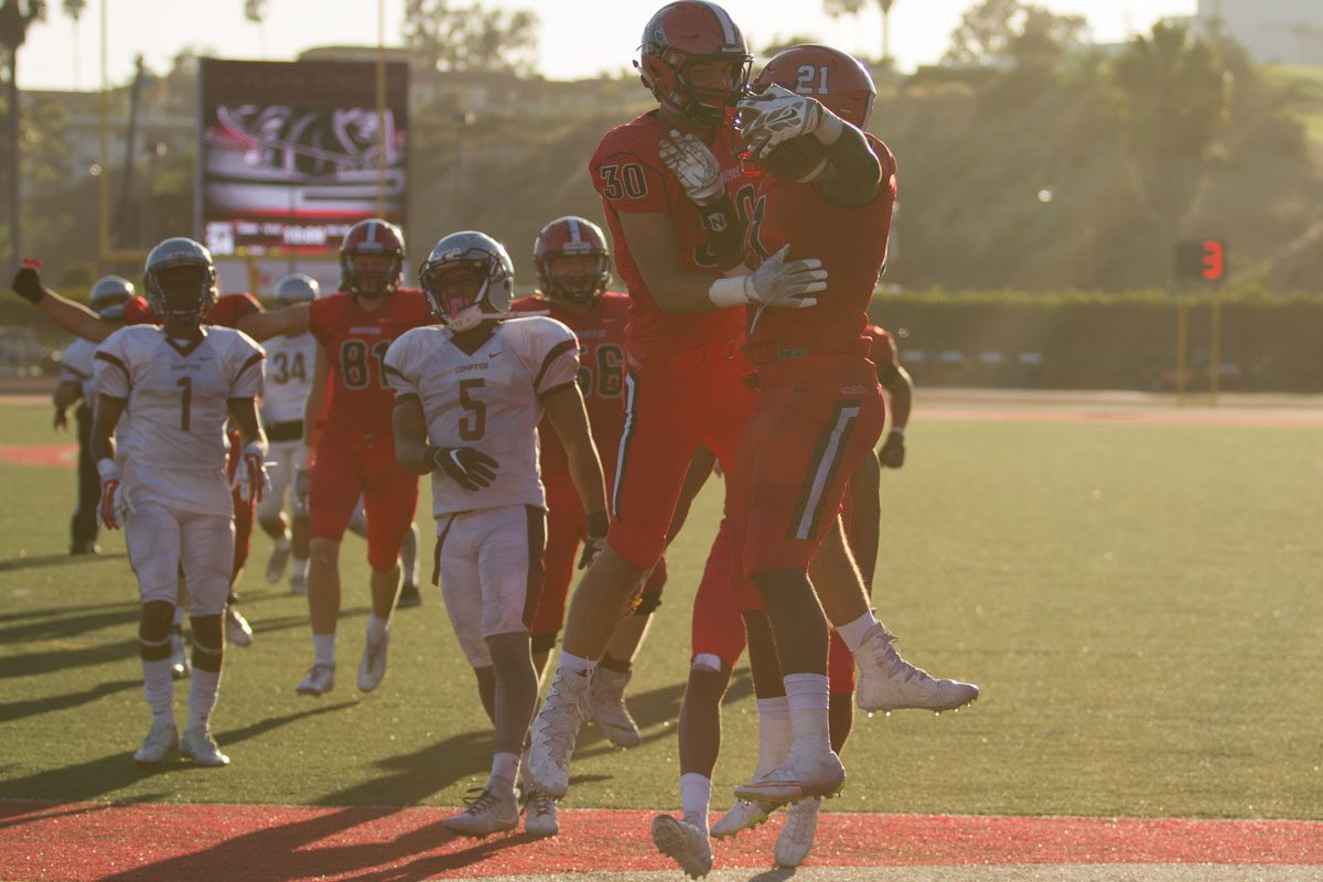 Running back Emmanuel Nwosu (No. 21) celebrating with teammate Cody Perry (No. 30) after scoring a touchdown against Compton College Saturday, Sept. 23., 2017, at La Playa Stadium in City College in Santa Barbara, Calif. Nwosus touchdown expanded the Vaqueros lead to 34-7.