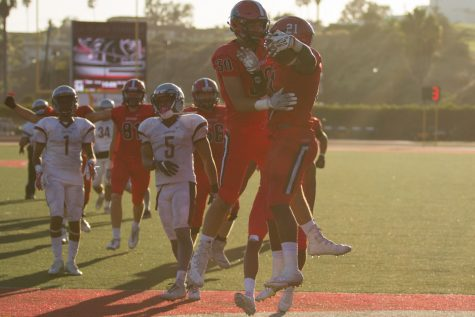 Running back Emmanuel Nwosu (No. 21) celebrating with teammate Cody Perry (No. 30) after scoring a touchdown against Compton College Saturday, Sept. 23., 2017, at La Playa Stadium in City College in Santa Barbara, Calif. Nwosu