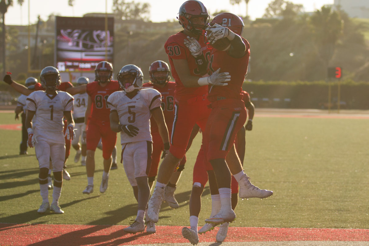 Running back Emmanuel Nwosu (No. 21) celebrating with teammate Cody Perry (No. 30) after scoring a touchdown against Compton College Saturday, Sept. 23., 2017, at La Playa Stadium in City College in Santa Barbara, Calif. Nwosu's touchdown expanded the Vaqueros lead to 34-7.