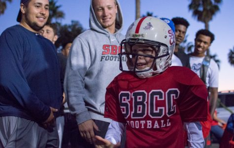 (From left) Defensive linemen for the City College football team Timothy Nunez and Tristan Harris high five 9-year-old Beckett Smalldon, dressed as a City College football player, during the Trunk or Treat event Friday, Oct. 27, held at the parking lot adjacent to La Playa Stadium.