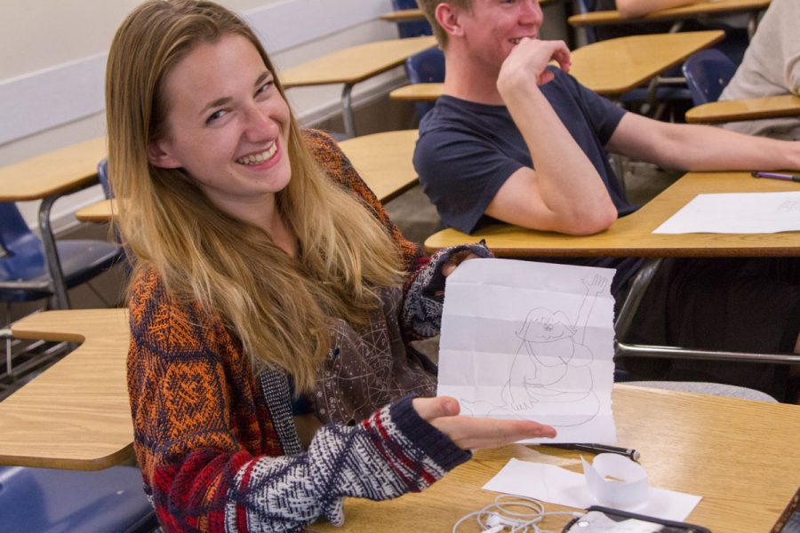 Club member Emily Hayman holds up her example of her mermaid drawing using grid lines Thursday, Oct. 18, in Interdisciplinary Center Room 106.