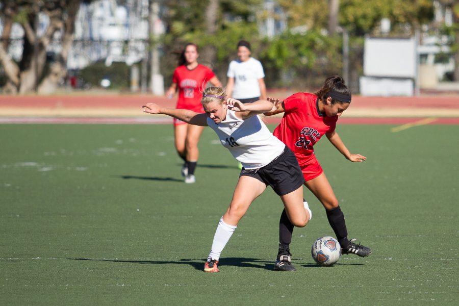 Women's soccer team member, Elizabeth Estrada (No. 22) of the Santa Barbara City College Vaqueros, regains control of the ball from Cuesta College Cougar Brenae Damery (No. 16) Tuesday, Oct. 24, at La Playa Stadium.