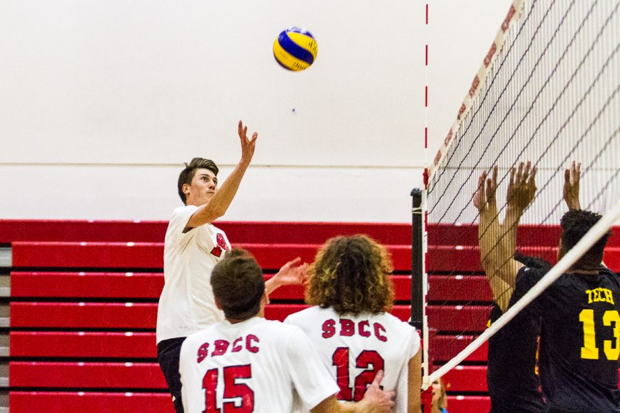 "Kyle Skinner (No.14) pokes the ball over the Los Angeles Trade-Technical College defense on Feb. 21, at the Sports Pavilion, in Santa Barbara. ""My passing was pretty good, but not as good as I wanted it to be,"" Skinner said after the Vaqueros dominated LA in 3 sets."