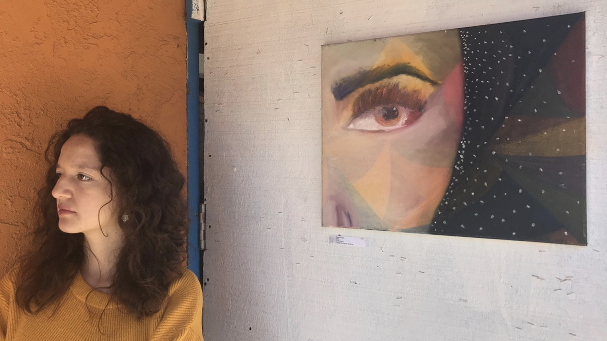 """Camila Rodriguez stands next to her acrylic painting """"Slowly Freed"""" as guests come to the ART 118 pop-up show on Friday, March 23, at the Biko House in Isla Vista."""