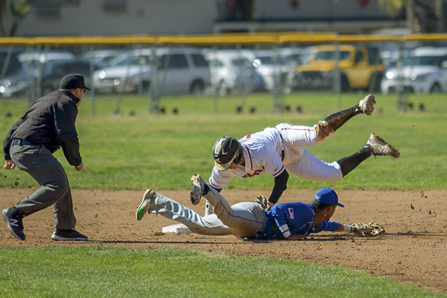Zack Stockton (No. 12) jumps to second base, while the second basemen from Oxnard College attempts to tag him out on Thursday, March 15, at Pershing Park in Santa Barbara, Calif. Stockton successfully stole second base.