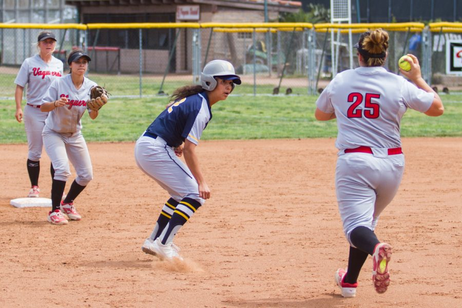 City College third baseman Kayla Sanchez (No. 25) attempts to tag out Sabrina Anguiano (No. 12) of Fullerton College who is caught in a rundown between second and third base at Pershing Park on Saturday. Anguiano ended up safe on second base and the Hornets swept the Vaqueros in a doubleheader 5-3 and 4-2.