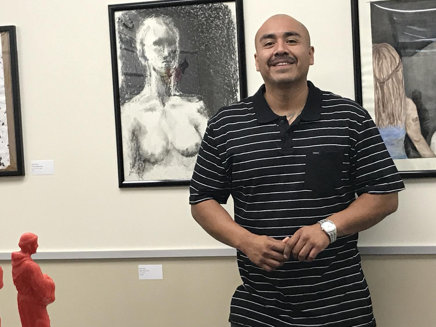 "Commencement speaker Alberto Lule stands in front of his pop-up art show, ""The Monster in my Closet"" located in the Equity Center May 11, 2018. Lule was previously incarcerated and said he found a passion for art in prison, which lead him to obtaining three art degrees."