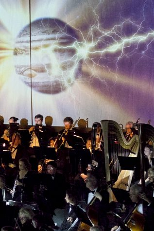 "The planet Jupiter is displayed on screen while the orchestra performs Gustav Holst's ""The Planets.""This was the first time the music department used projected visuals for an orchestra performance."