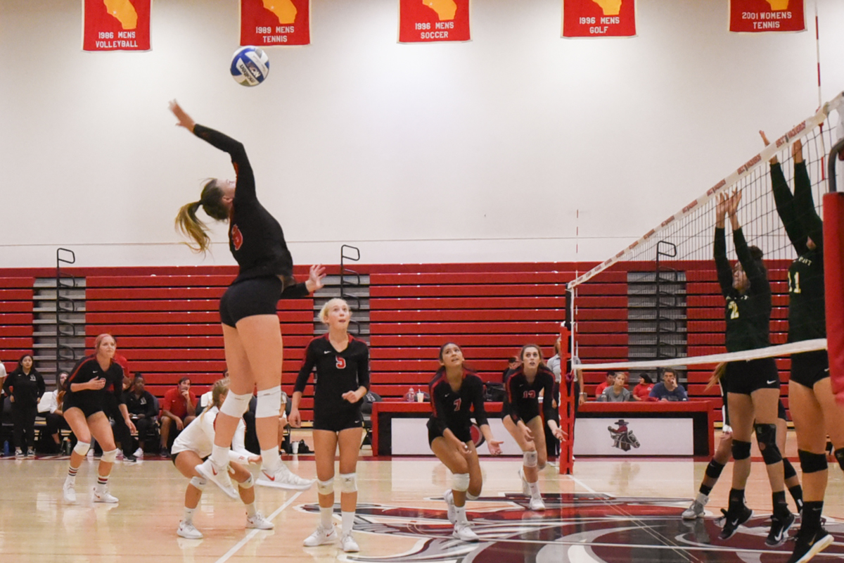 Kate Willingham (No. 8) spikes the ball against Grossmont Community College at the Sports Pavilion gym at City College on Saturday, Sept. 22.