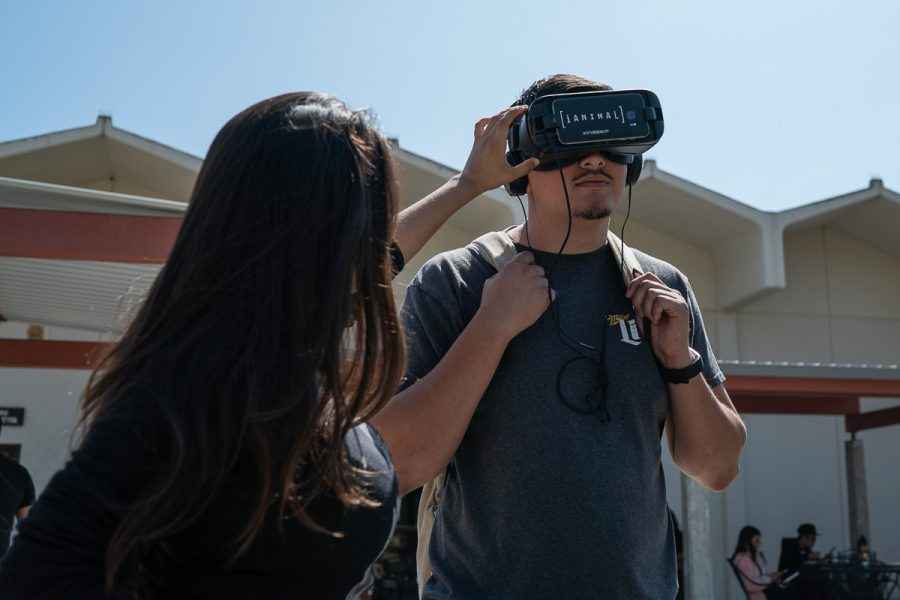 Alicia Alcasas helps a student start a virtual reality experience where the viewer is placed in the slaughterhouse assembly line with the livestock at City College in Santa Barbara Calif., on Monday, Sept. 24, 2018. The VR headset experience was part of the Animal Rights Club event.
