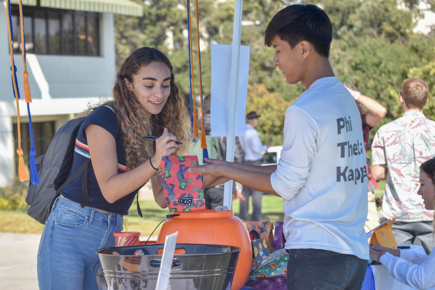Newara Brosan-Faltas addresses a candy bag with the help of Christopher Lee, Phi Theta Kappa president, for the Phi Theta Kappa Trick or Treat fundraiser on Thursday Oct. 24, 2018, at City College in Santa Barbara Calif. All of the fundraiser proceeds will be donated to the Alzheimer's Foundation.