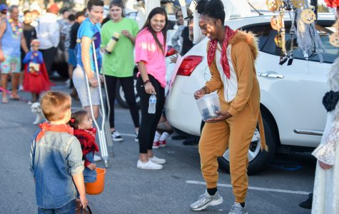 Megan Moore, dressed up as lion, passes out candy to Mila Boardman during the second annual Trunk or Treat event held at the parking lot adjacent to La Playa Stadium on Friday, Oct. 26, at City College in Santa Barbara Calif. The free event was hosted by the City College Athletic Department to give children a safe place to trick-or-treat.