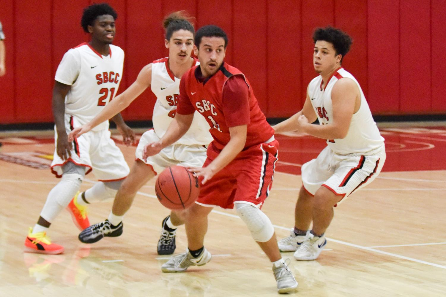 Robert Hutchins (center) alumni from the years 2016 and 2017, looks to pass the ball at the 45th annual alumni basketball game on Thursday, Dec. 6, in the Sports Pavilion gym at City College in Santa Barbara Calif. The current City College team beat the alumni 87-83.