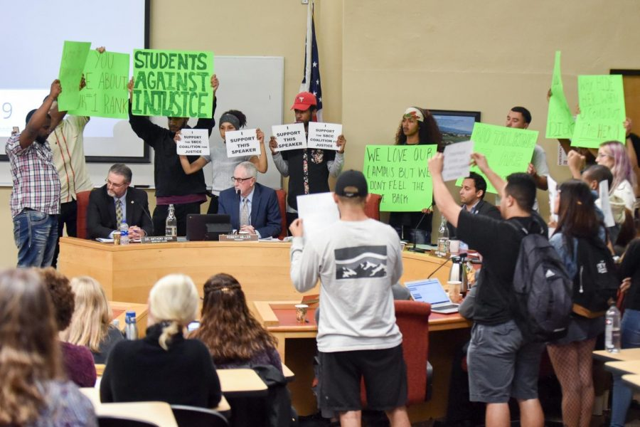 Student protesters surround Board of Trustees members Thursday while holding signs in silent protest of the return of Vice President of Business Services Lyndsay Maas to the college. Maas has been on unpaid leave since November after using the un-abbreviated version of the n-word at an equity meeting.