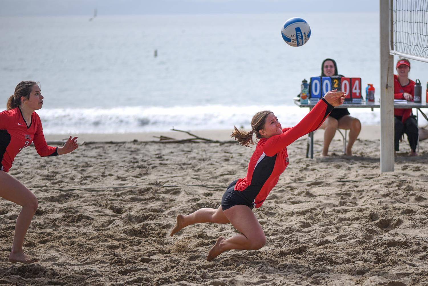 Maddie Meyer (No. 4) dives to save the ball with Michelle Orgel (No. 3) following close behind on Friday March 1 at East Beach in Santa Barbara.