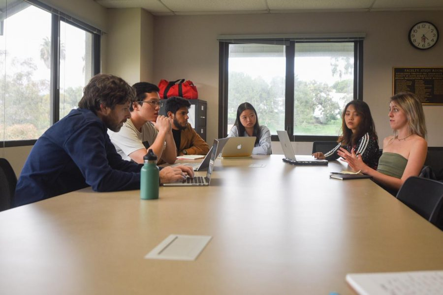 "From left, professor Mark Bobro and students, Seine Ham, Jorge Caballero Naranjo, Zongchan Chen, Myrth Tan and Anna Love prepare for the ""International Business Ethics Competition"" in the Luria Library."