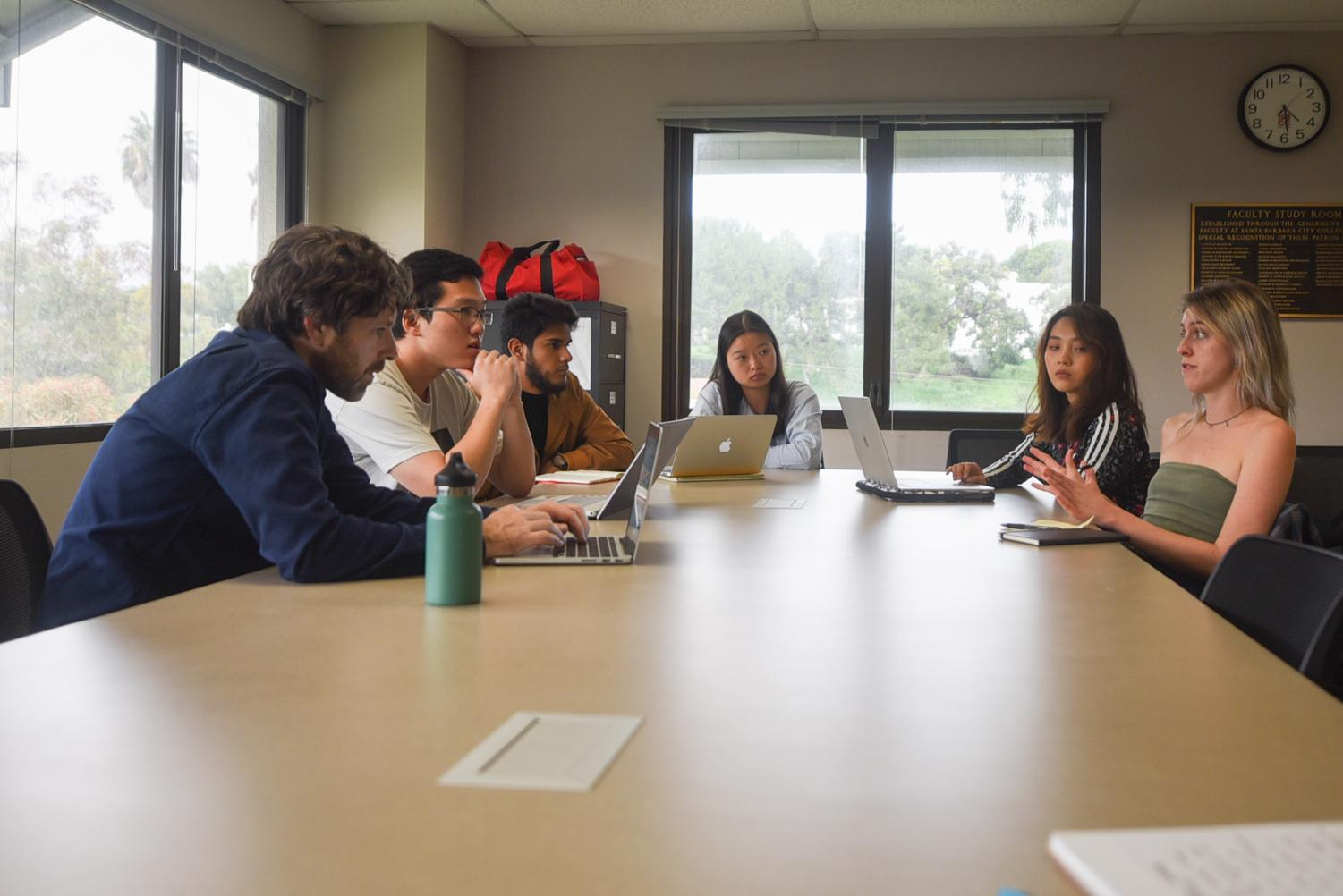 """From left, professor Mark Bobro and students, Seine Ham, Jorge Caballero Naranjo, Zongchan Chen, Myrth Tan and Anna Love prepare for the """"International Business Ethics Competition"""" in the Luria Library."""