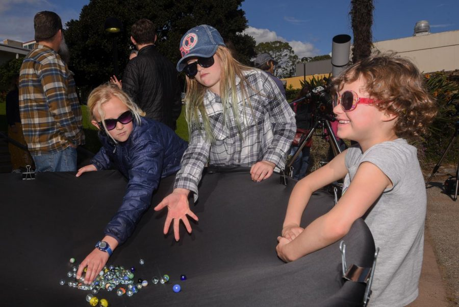 """From left, Marlee Cattanach, Delany Hansen, and Emma Clarke experiment with a black-hole replication telescope at the """"Science Discovery Day"""" on Saturday, March 8, 2019, on East Campus at City College in Santa Barbara, Calif."""