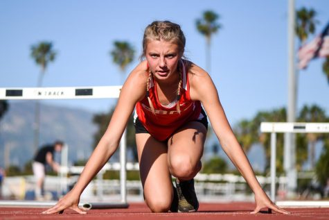 Caroline Smith kneels down, how she would before a race, on Friday, April 12, 2019 at La Playa Stadium at City College in Santa Barbara, Calif.
