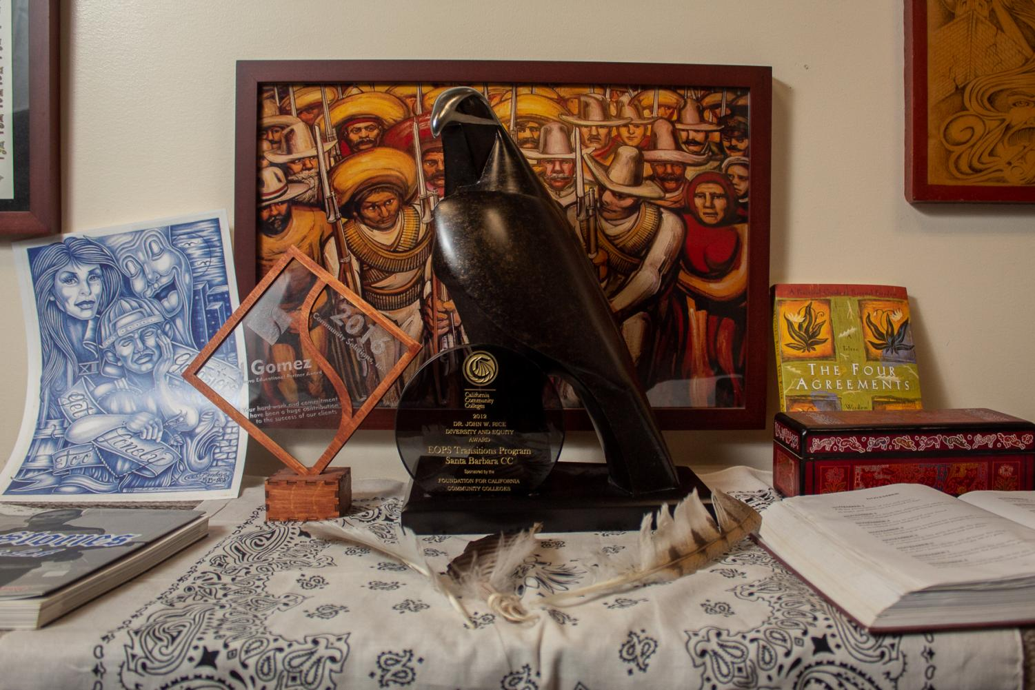 Some of Noel Gomez's awards and artwork in his office in the Student Services Building on Friday, Nov. 8, at City College in Santa Barbara, Calif. The hawk trophy (center) was awarded to EOPS for the transition program.
