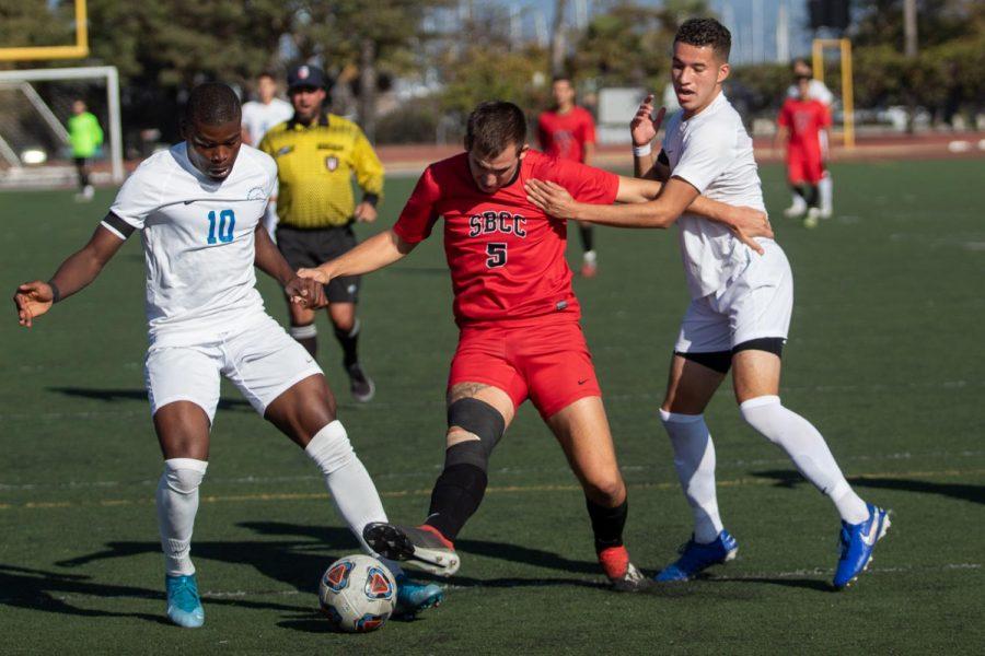 Roni Spektor (No.5) trying to force his way through two Santa Monica College defenders on Sunday, Nov. 10, 2019, at La Playa Stadium at City College in Santa Barbara, Calif.