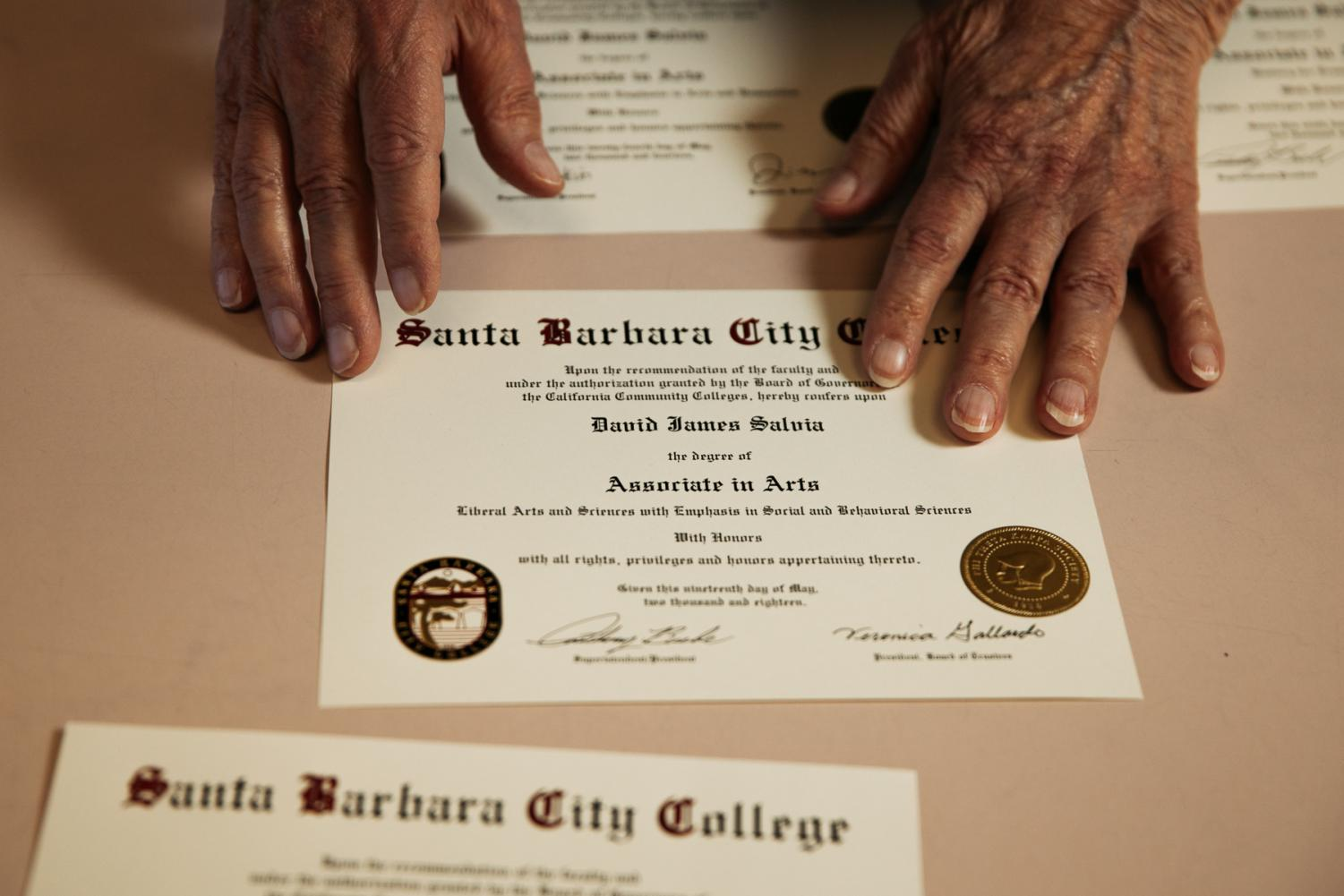 David Salvia arranges his degrees and certificates on a table in the Luria Library on Thursday, Oct. 31, in Santa Barbara, Calif.