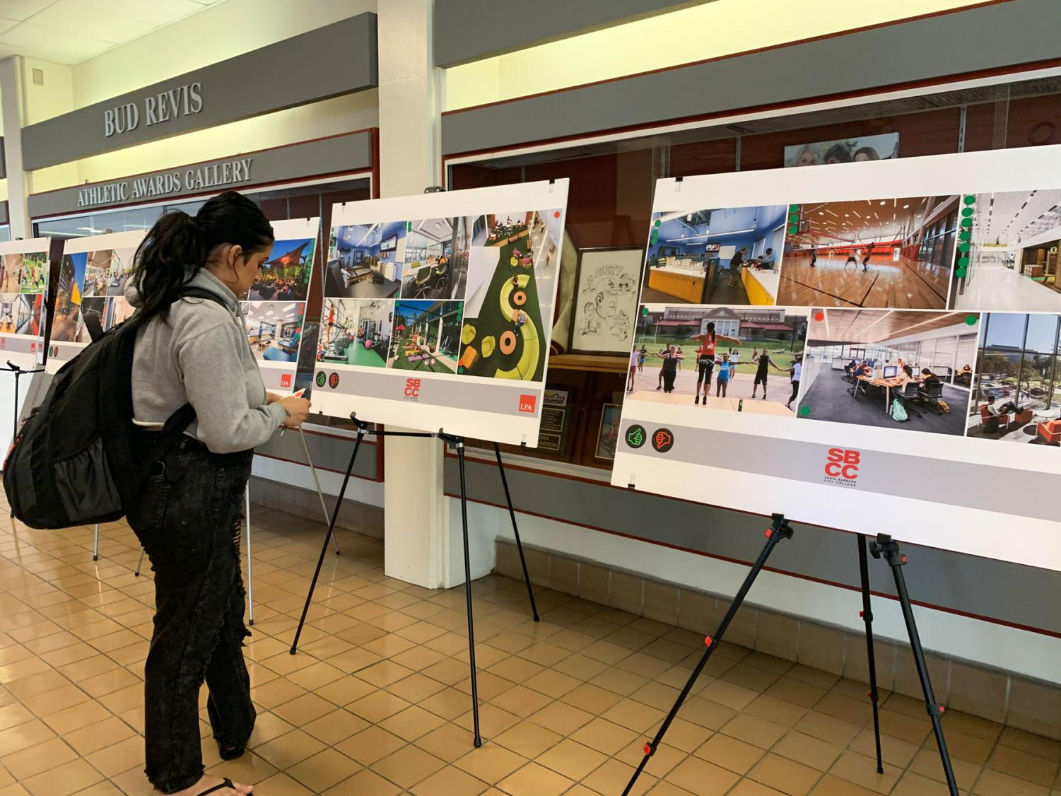 Paula Muñoz observes past project designs similar to the upcoming renovation of the Sports Pavillion on Wednesday, Nov. 13, 2019, in the Sports Pavilion at City College in Santa Barbara, Calif.