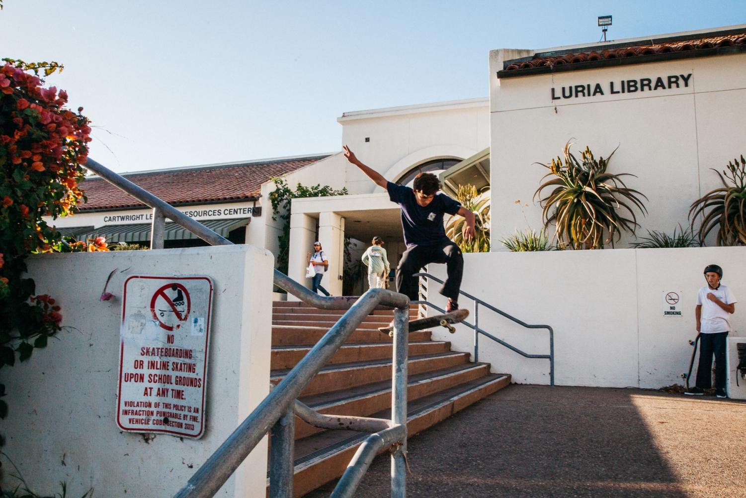 Emmett Wallop ollies a five stair on Tuesday, Nov. 19 outside the Luria Libary. Campus security arrived shortly to remove wallop and friends from the premises.