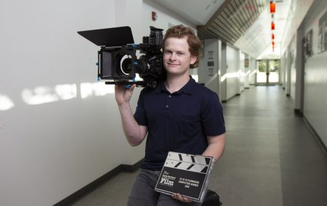 City College student Will Hahn sits in the hallway of one of his favorite buildings on campus, the Humanities building, holding the award for Best Director from the Santa Barbara Film festival with his camera on Feb. 18, 2020 at City College in Santa Barbara, Calif.
