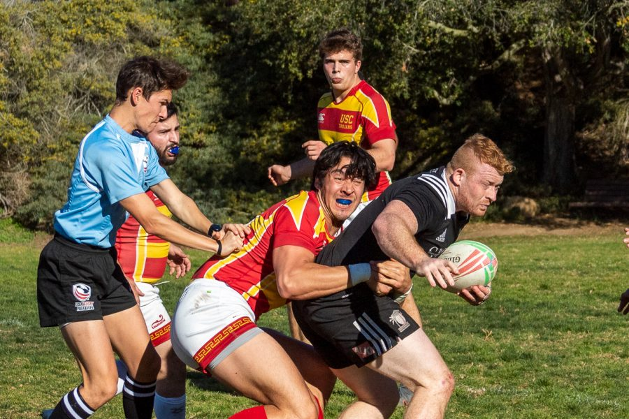 Patrick Moulder (No.7) pushes through multiple Trojans during the Santa Barbara Rugby Academy match against the University of South California on Saturday, Feb. 1, 2020, at Elings Park in Santa Barbara, Calif. The Academy beat the Trojans 78-7.