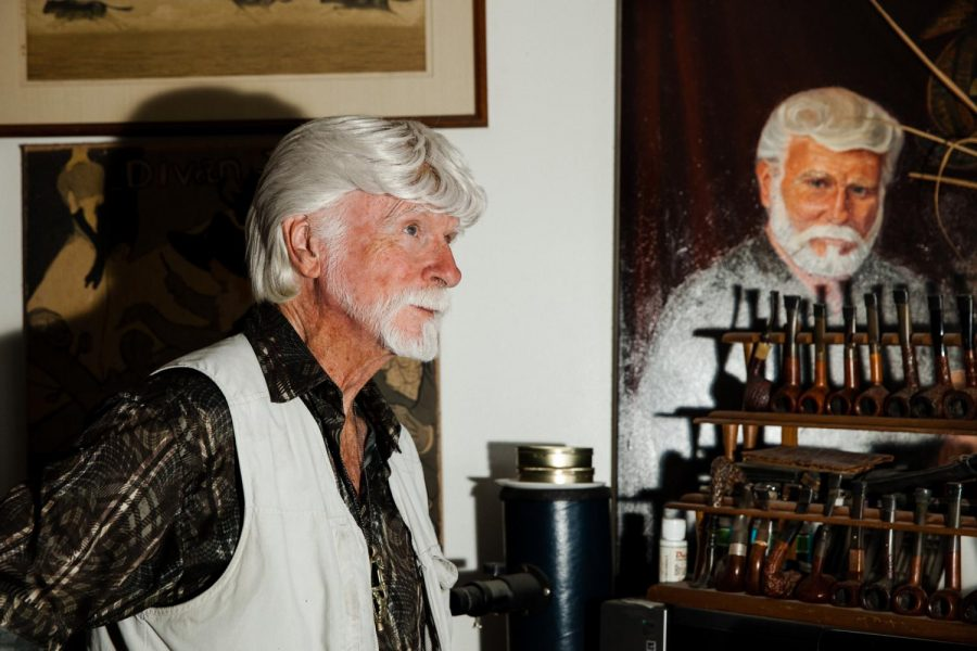Ron Atwood stands in his home office with a portion of his antique tobacco pipe collection and a self portrait painting from 1998 done by a friend.