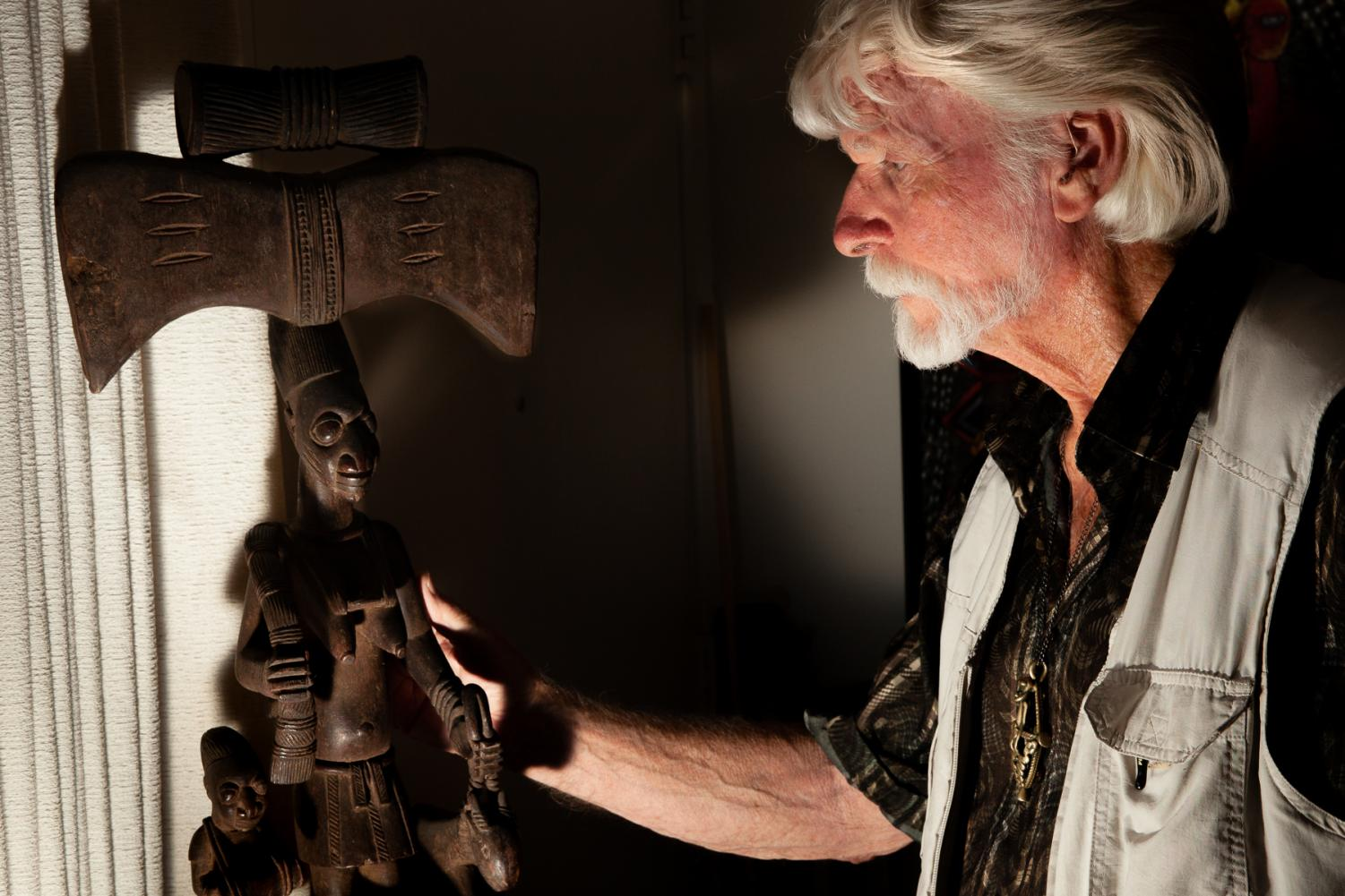 Ron Atwood admires a Shrine sculpture to the powerful Shango god of thunder of a female worshiper with a thunder celt headpiece and talking drum, one of his most valuable and prized pieces.