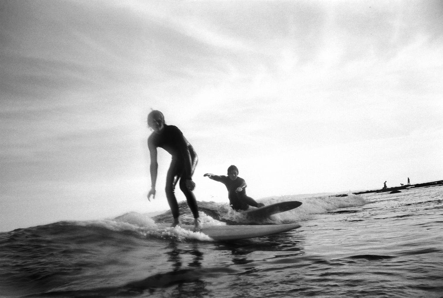 Luke Williams (right) and younger brother Jake Williams share a wave at Leadbetter Beach on Wednesday, Feb. 26 in Santa Barbara, Calif. Luke and Jake grew up in Ventura, Calif., and have been surfing since they were young teenagers.
