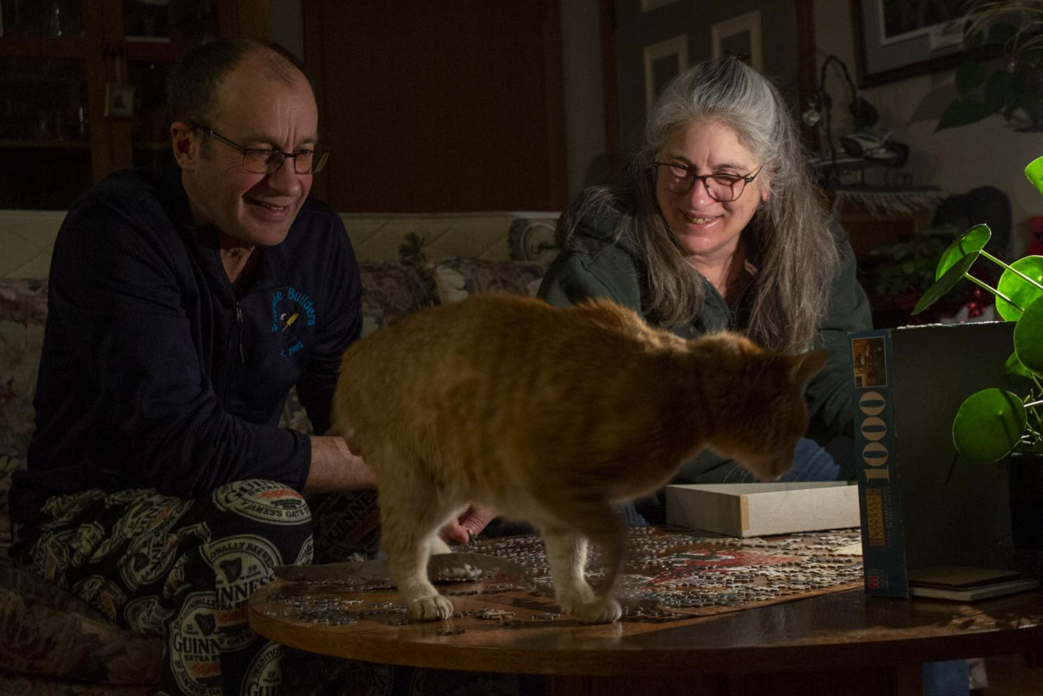 Mitch Scrage and Terese Brunner share a laugh over their cat Sully jumping on the table and on top of the puzzle they started together on April 6, 2020 at their home in New Holstein, Wis. Throughout the uncertainty of shelter in place orders Brunner and Schrage have been enjoying the extra time together.