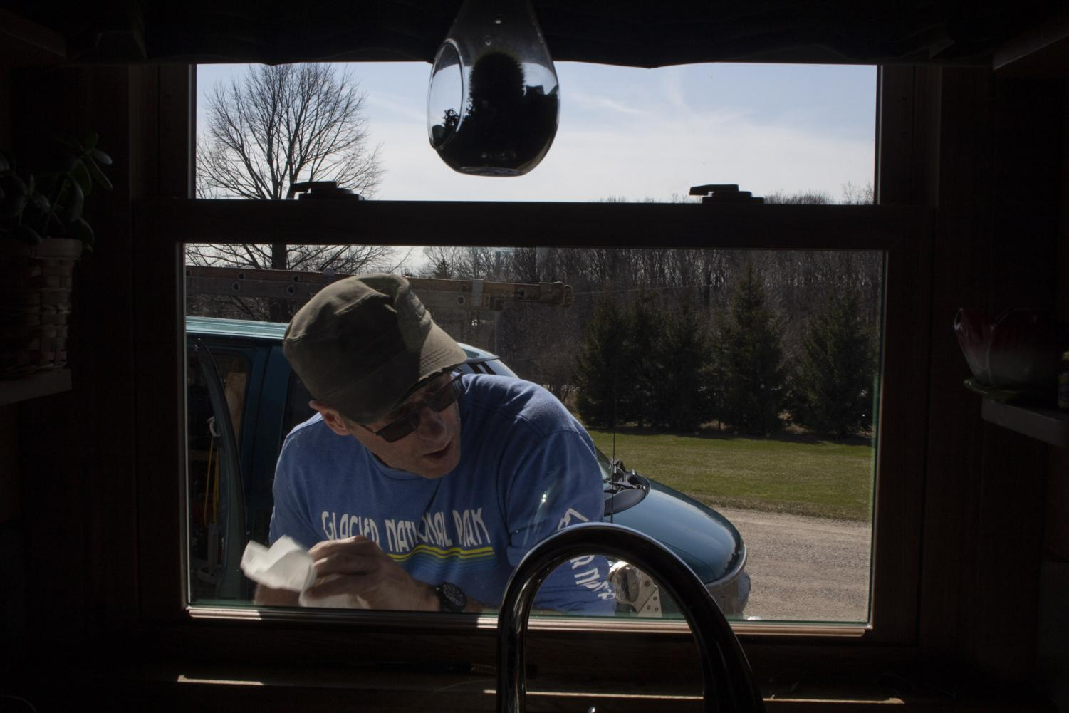 Mitch Schrage wipes the sawdust off a new screen he installed on his house on April 2, 2020, at his home in New Holstein, Wis. Schrage is used to work picking up this time of year, and with the shelter in place order in act, his business has not been affected at all, if anything has increased.