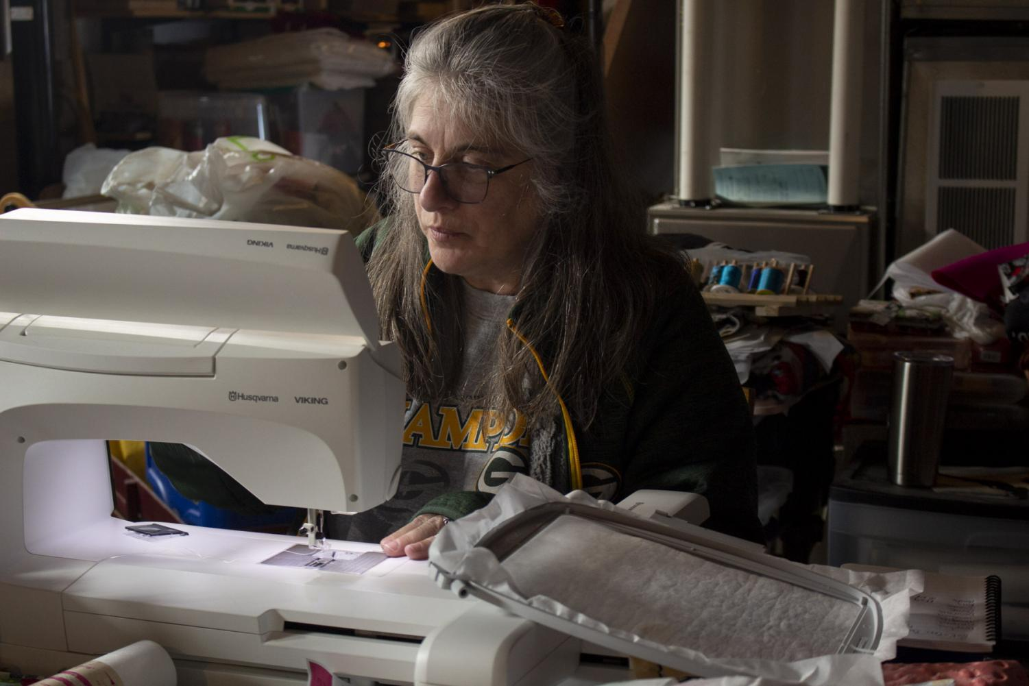 Terese Brunner changes the bobbin on her embroidery/sewing machine on April 2, 2020 at her home in New Holstein, Wis. Brunner is taking advantage of free time and has been testing out new embroidery designs and finishing up a baby blanket for her expecting goddaughter.