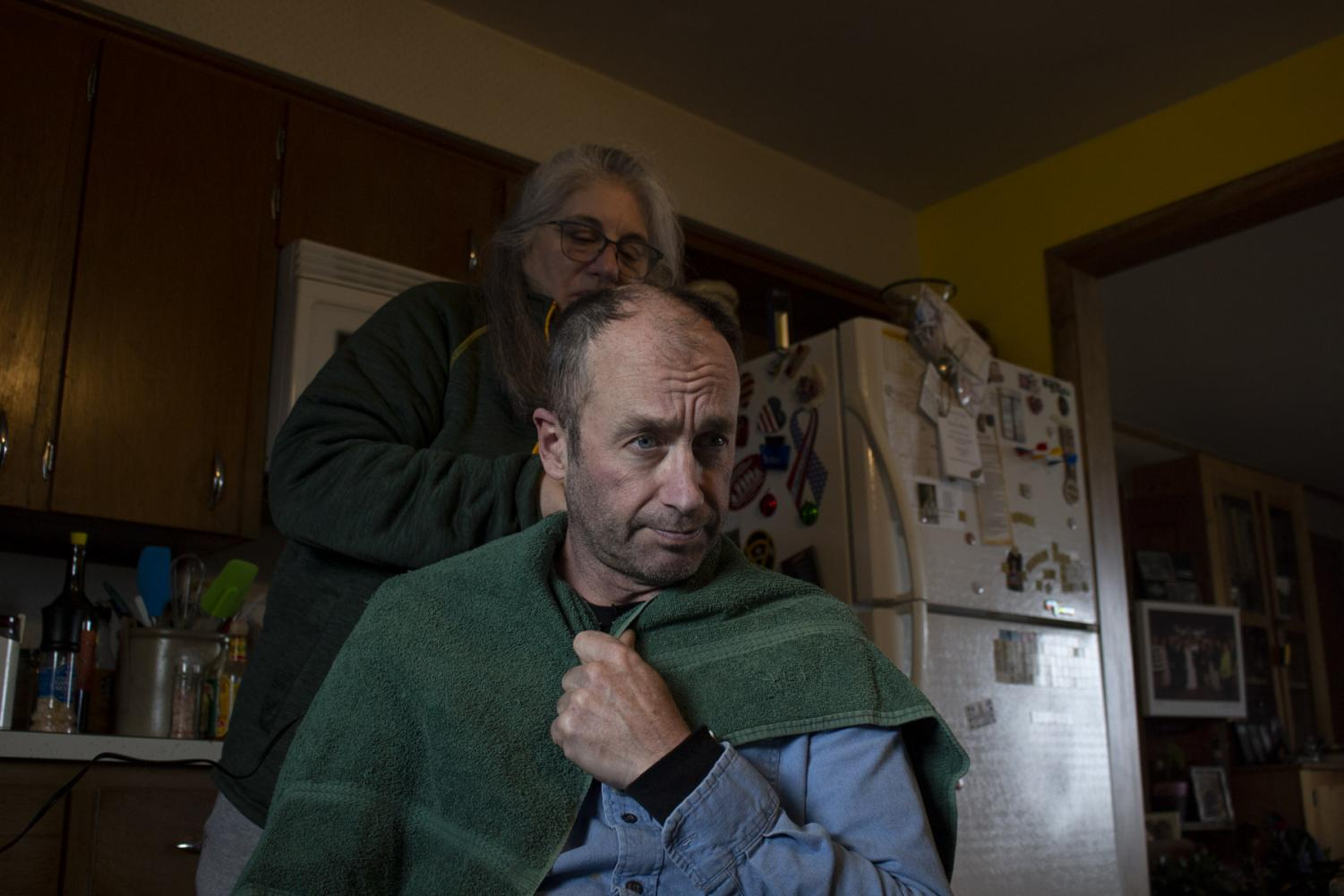 Terese Brunner cuts Mitch Schrage's hair at home while barber shops remain closed in the area on April 15, at their home in New Holstein, Wis. Schrage occasionally gets his haircut at a barbershop and usually has Brunner trim his hair in-between visits.