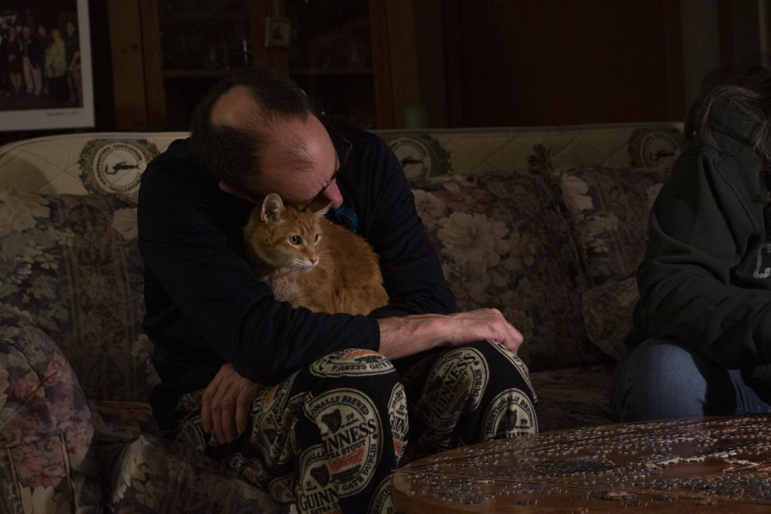 Mitch Schrage takes a break from putting a puzzle together with Terese Brunner to hug their cat Sully on April 6, 2020 at their home in New Holstein, Wis. Schrage finds comfort in the company their pets provide during these stressful times.