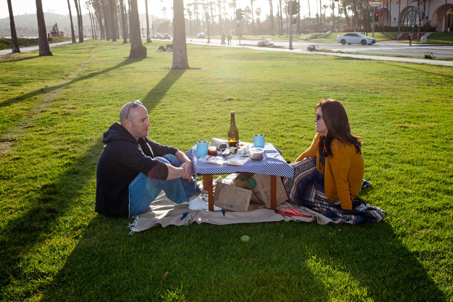 "As restaurants close or offer take-out only Nate Tackerman and Jenny Brice share a picnic at Chase Palm Park to get out of the house on Saturday, April 4, in Santa Barbara, Calif. ""We're just hanging out here since everything is pretty much closed,"" Tackerman said."