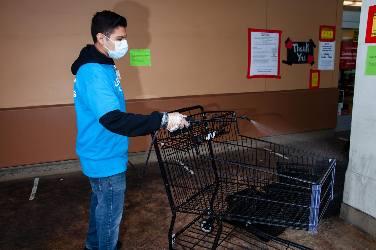 Dario Alonso sprays a disinfectant solution on shopping carts at Vons Supermarket on The Mesa on Thursday April 9, in Santa Barbara, Calif. Alonso started working two weeks ago to help his mother pay rent after she lost her job due to coronavirus precautions.