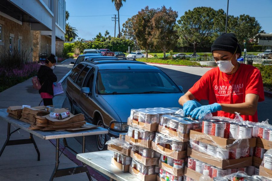 From left, Equity Department employees Alondra Lazaro and Juwan Vega work the drive-through food drive line on Wednesday, April 1, 2020 on the West Campus roundabout at City College in Santa Barbara, Calif. Lazaro took specific orders and asked questions for a survey while Vega and other employees bagged items for drivers and walk-up students.