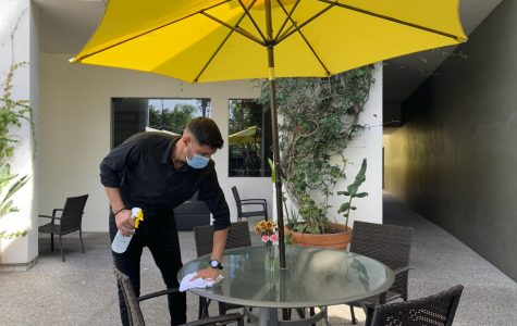 Server Luka Djuranovic wipes down a table during the sanitizing routine that is done after the customers are done eating on Sept. 17, 2020 at Crocodile Restaurant & Bar in Santa Barbara, Calif. Djuranovic regularly reminisces on when customers were able to come in and enjoy the bar and seats indoors during these routines.