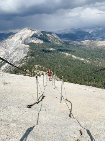 Angi Daus climbs up Half Dome on July 23, 2020 in Yosemite, Calif., using the support cables installed in 1920. The cables are an example of national parks becoming more convenient and accessible, but not without trade-offs.