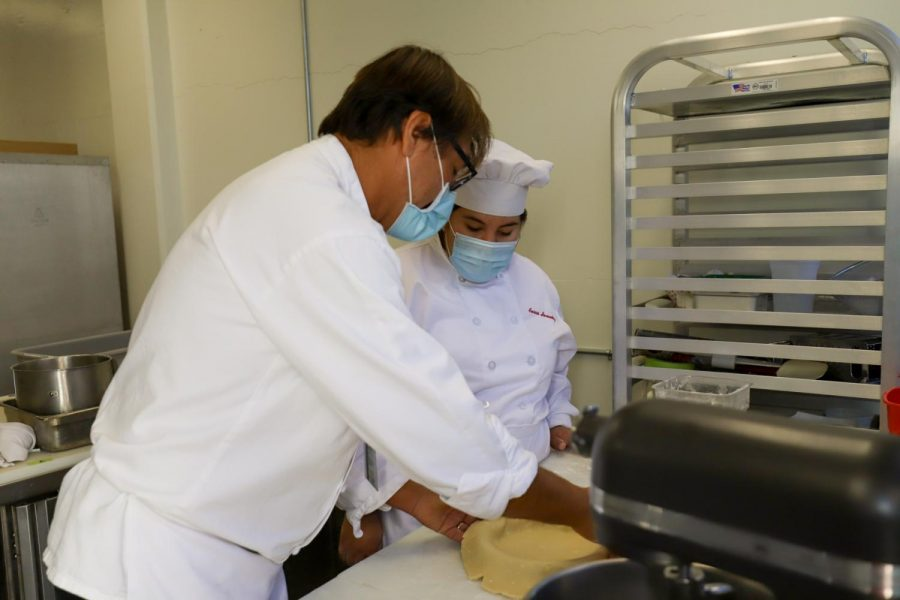 Chef Stephane Rapp helps Aurora Hernandez place her pie crust in the pan on Nov 24, in the Kitchen of the Cafeteria at City College in Santa Barbara, Calif. Class sizes are smaller because of the new class structures resulting in two LTA's and one teacher per student in the department.