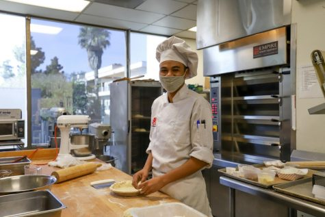 "Zuberi Sharp, a first year City College student, crimps the pie crust before placing it in the freezer to harden on Nov 24, 2020 in the Kitchen of the Cafeteria at City College in Santa Barbara, Calif. Chef Stephane Rapp said ""the energy has been extra positive"" because of students like Sharp."
