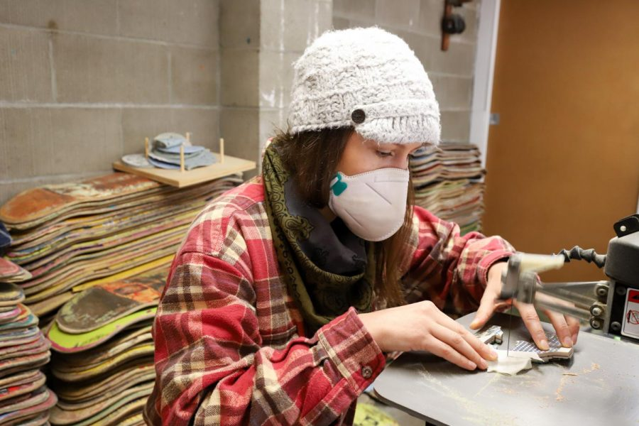 Inga Guzyte cuts off a small portion of a reflection piece of skateboard to add detail to a new portrait she started recently on Nov. 30 at her studio in Santa Barbara, Calif. Each detail of each of her artworks is inlaid and not just layered on top of each other.
