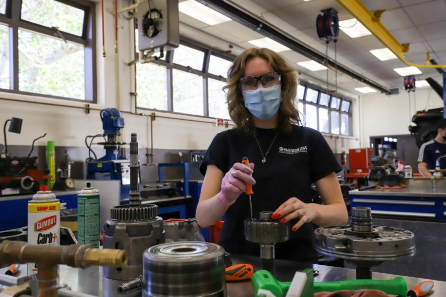 "Anna Grace Butler works on taking apart the transmission and putting it back together on Feb. 22 during the automotive lab in the MacDougall Administration Building at City College in Santa Barbara, Calif. ""I love this place, it's fixed a lot of my cars,"" said Butler, who has been a part of the Automotive department since she was 16 during middle college."