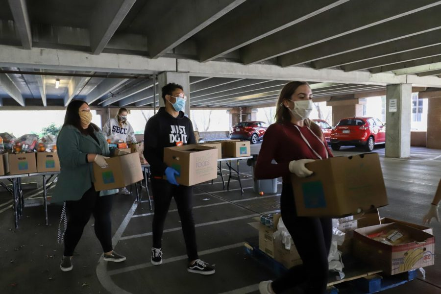 From left Aranzazu Magallanes, Jirehandre Bitangila, and Megan Mcgill carry boxes of pre-packaged fresh produce and non-perishables to a students car at the food distribution event in the West Campus Lot 5-1 on Wednesday Feb. 10, 2021 in Santa Barbara, Calif. The boxes have fresh produce such as celery, apples and milk along with items like bread and pasta as well.